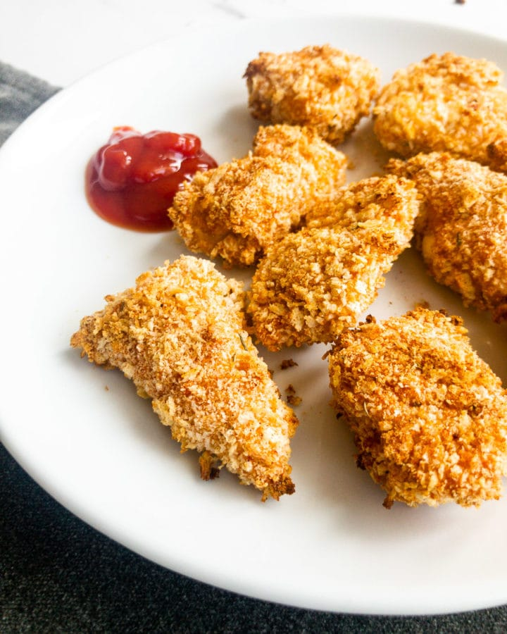 baked chicken nuggets on a plate with ketchup