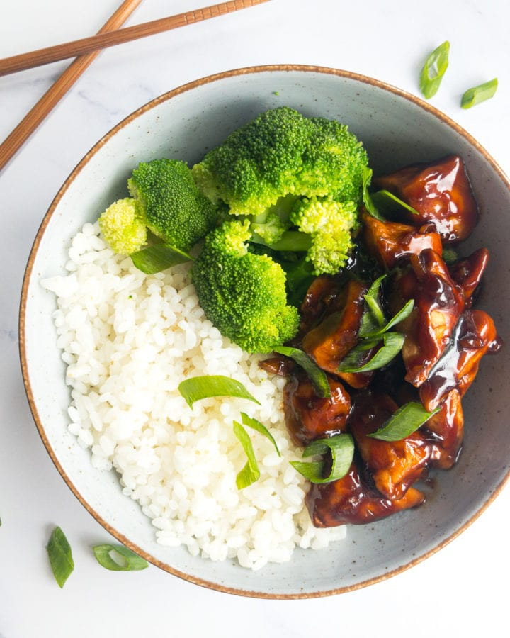 teriyaki chicken with rice and broccoli in a bowl next to chopsticks