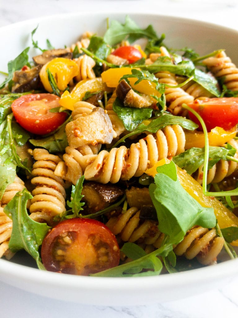 the best pasta salad with red pesto in a bowl