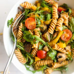 the best pasta salad with red pesto in a white bowl with a fork