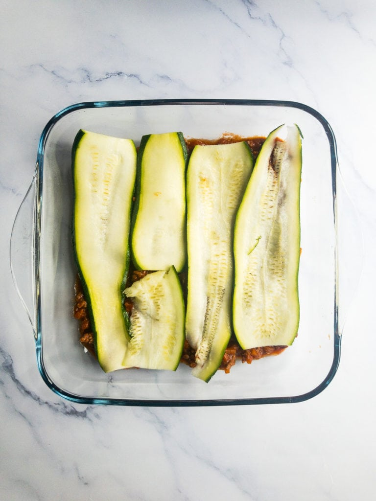 bolognese topped with zucchini slices in a casserole dish