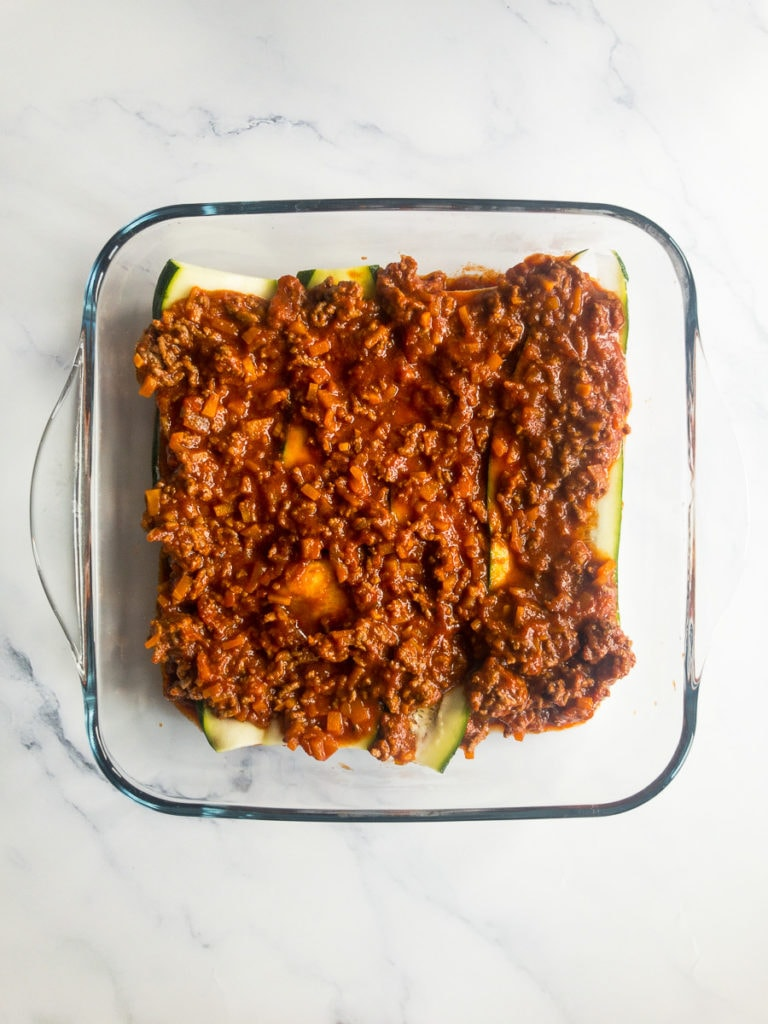 bolognese and zucchini slices topped with bolognese in a casserole dish