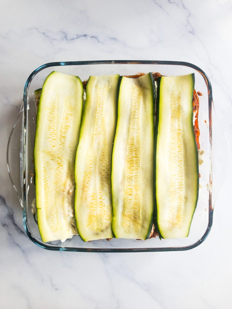 lasagna in the making topped with zucchini slices