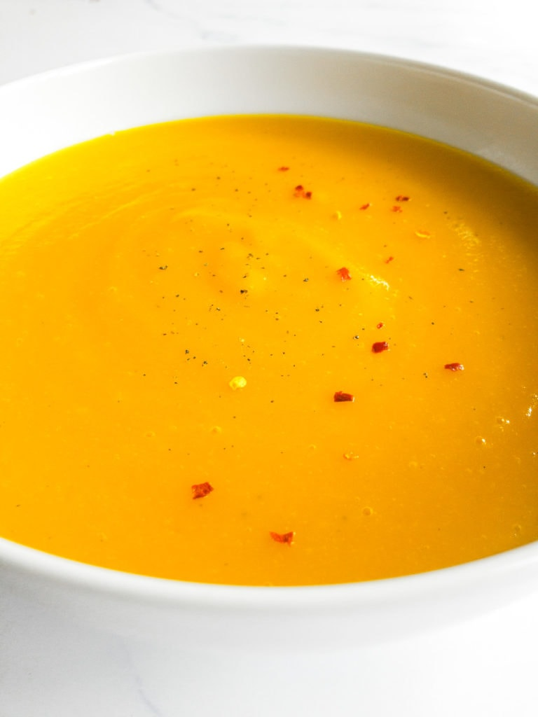 creamy carrot potato soup in a white bowl