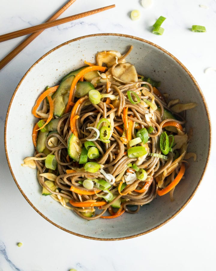 cold soba noodle salad with ginger-soy-dressing in a bowl on a table with chopsticks