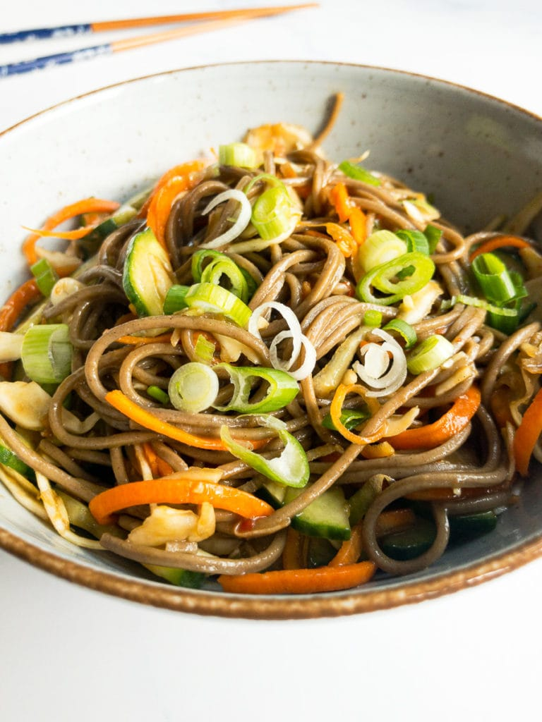 cold soba noodle salad with ginger-soy-dressing in a bowl with chopsticks in the background