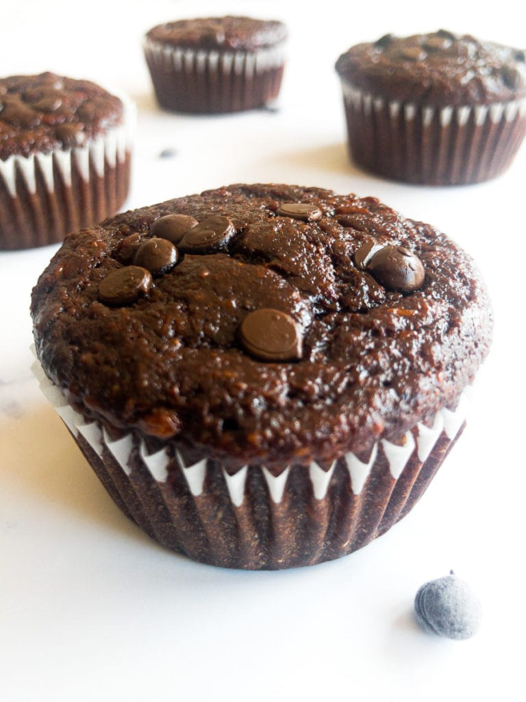 four double chocolate banana oatmeal muffins on a table