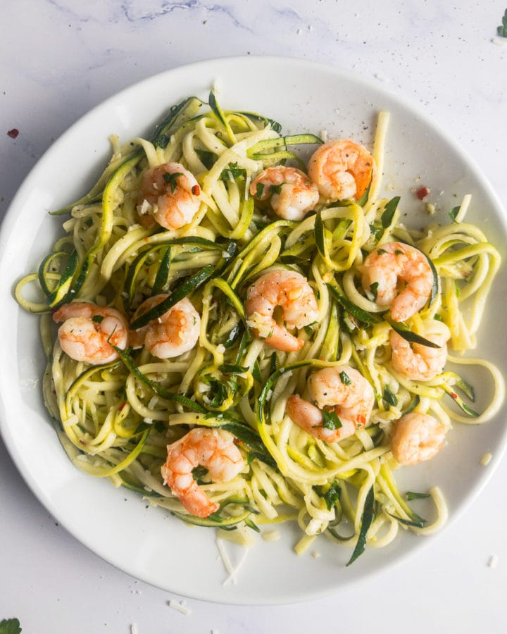 zucchini noodles with garlic shrimp on a white plate