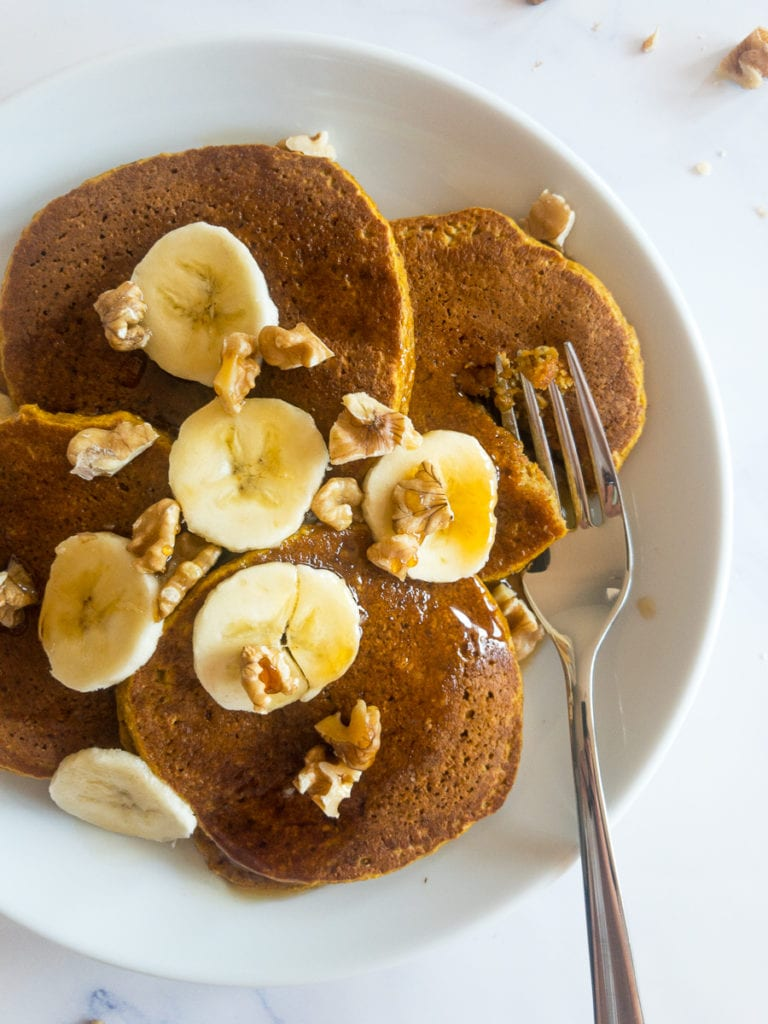 gluten free pumpkin pancakes on a white plate with a fork