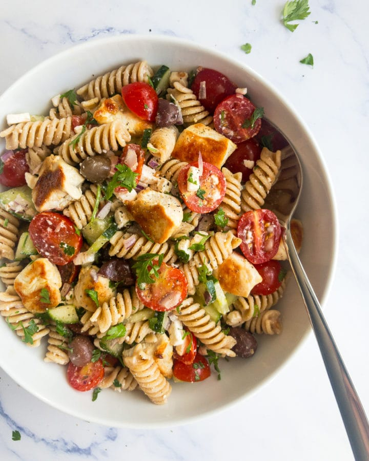 greek chicken pasta salad in a white bowl with a spoon