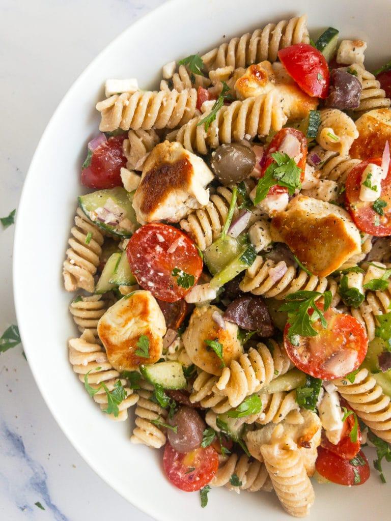 greek chicken pasta salad in a white bowl