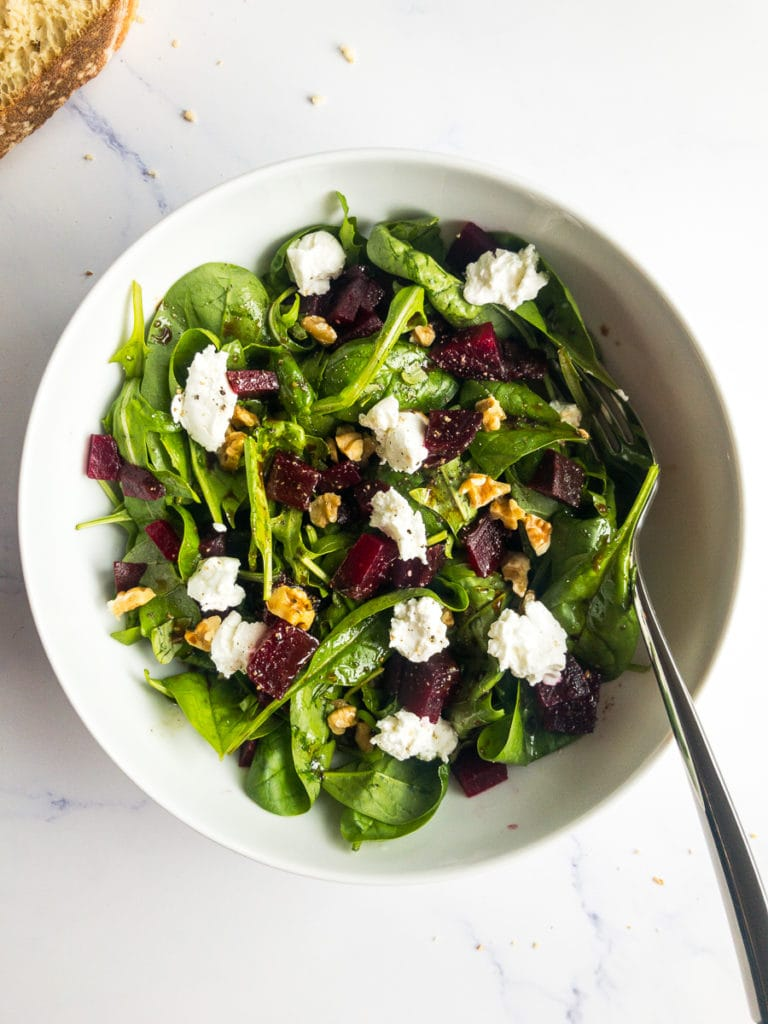 beet and goat cheese salad in a white bowl with a fork and breadcrumbs on the table