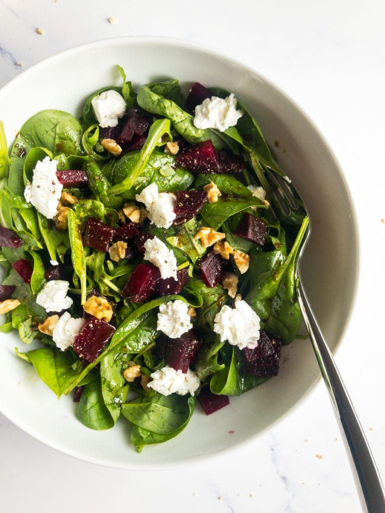 beet and goat cheese salad in a white bowl with a fork