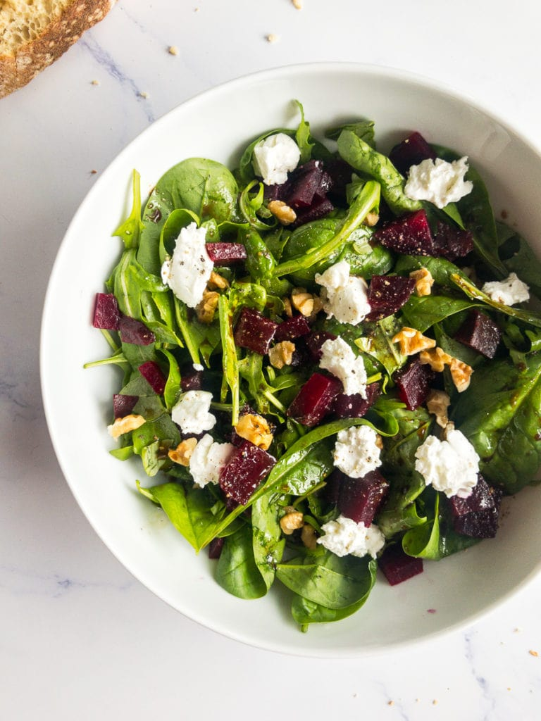 beet and goat cheese salad in a white bowl and bread on the table