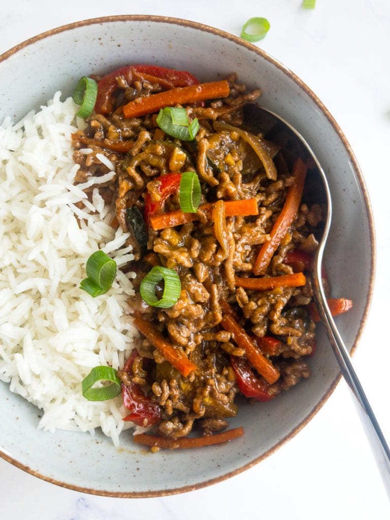 ground beef stir fry with rice in a bowl with a spoon
