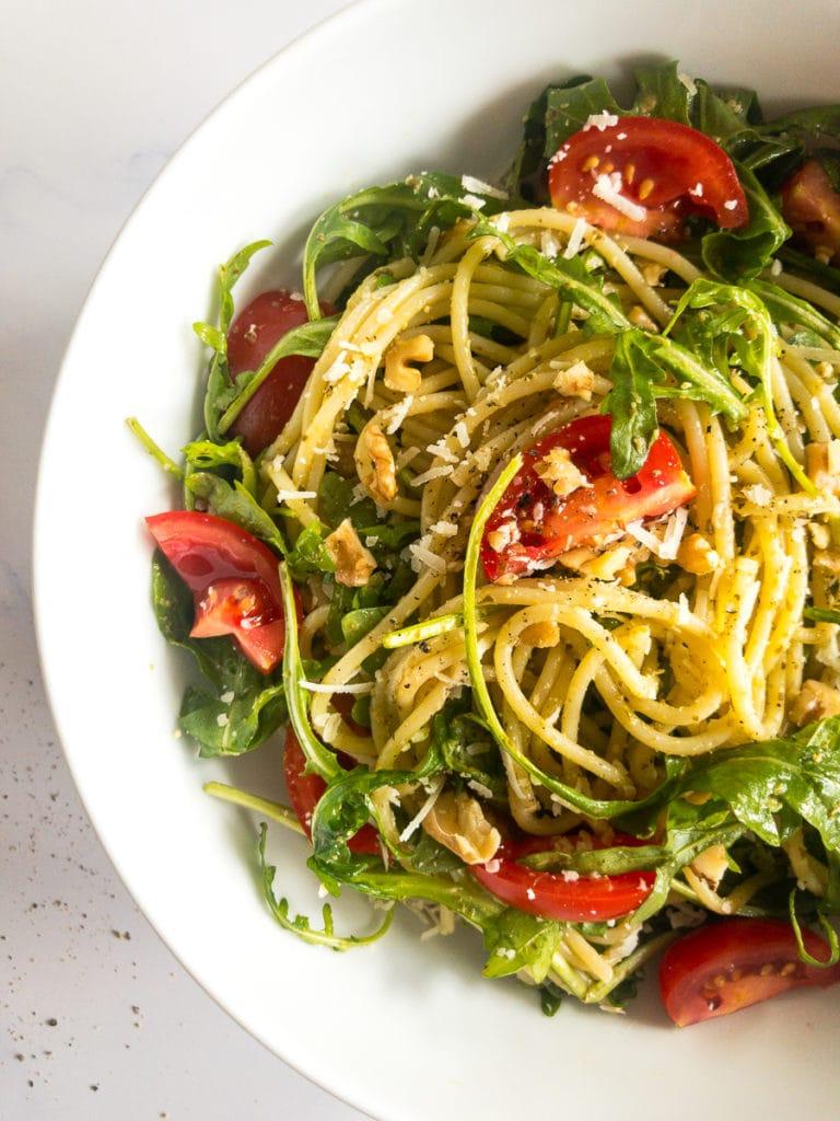 pesto spaghetti salad in a white bowl