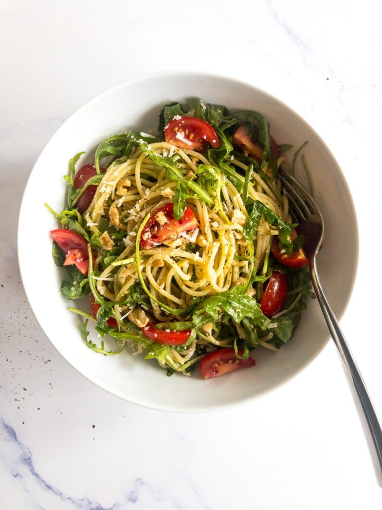 pesto spaghetti salad in a white bowl with a fork