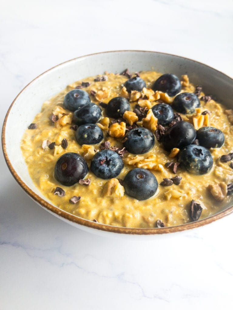 pumpkin pie overnight oats with blueberries and walnuts in a bowl
