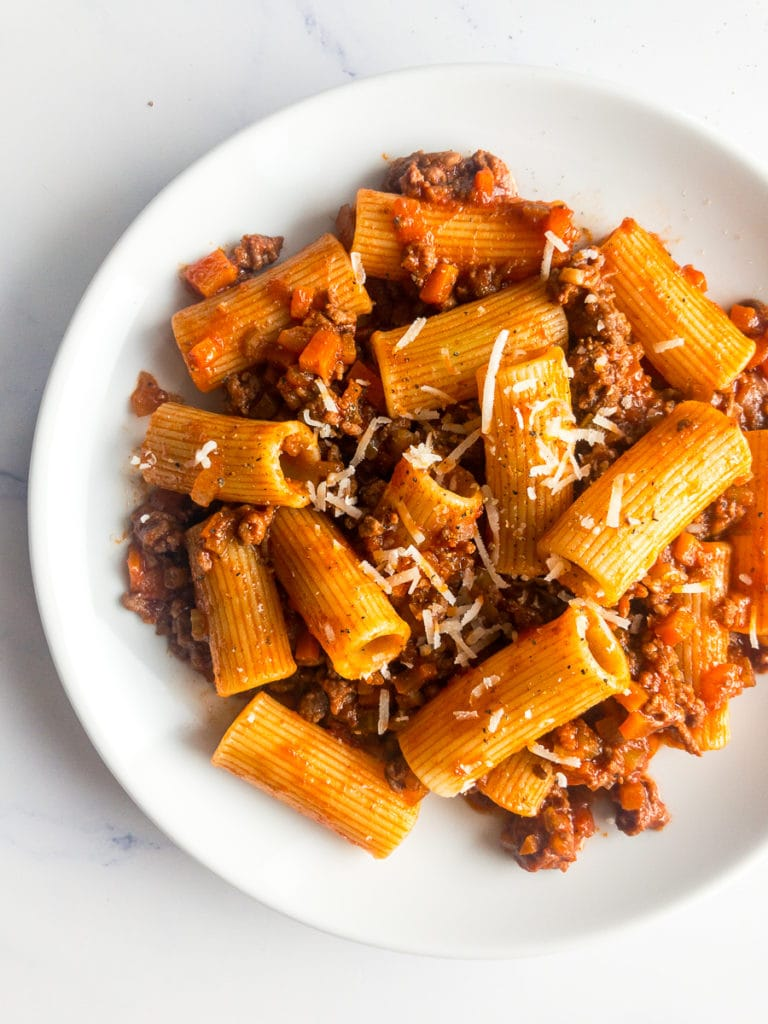 rigatoni bolognese on a white plate with a fork