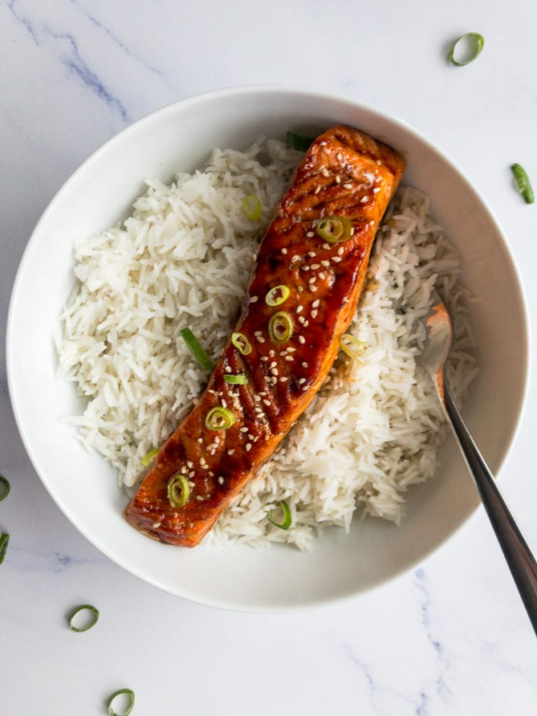 teriyaki salmon in a white bowl with a fork