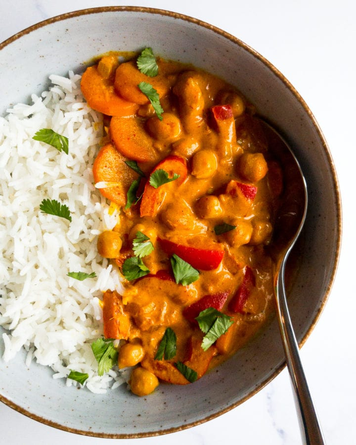 coconut chickpea curry in a bowl with rice and a spoon