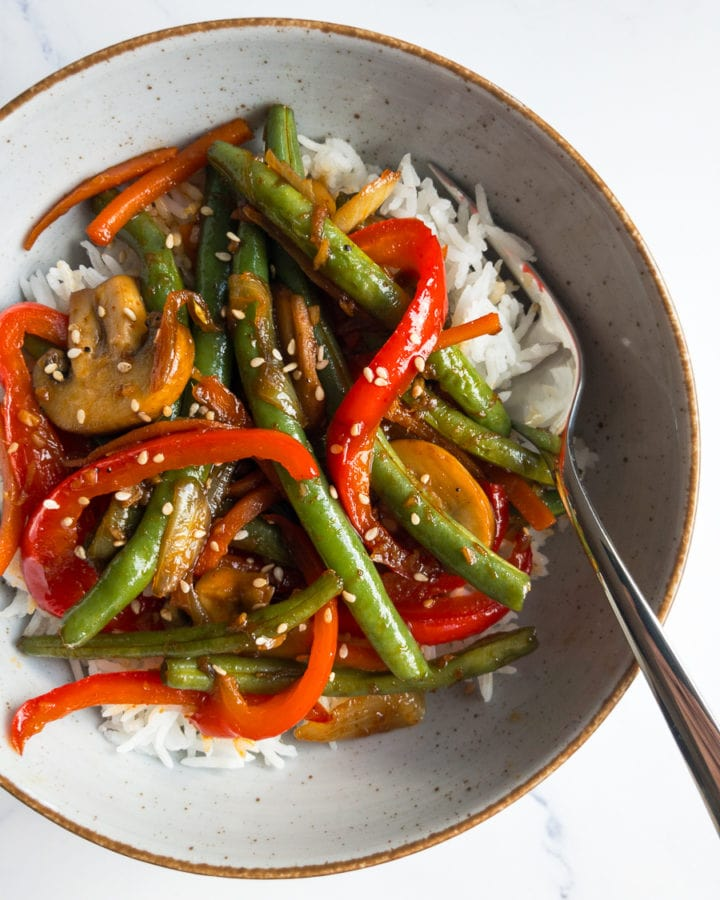 ginger soy vegetable stir fry and rice in a bowl with a fork