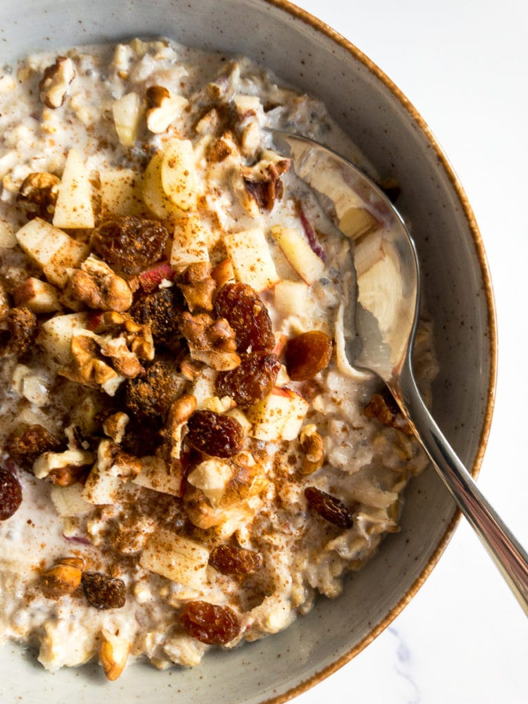 apple cinnamon overnight oats in a bowl with a spoon