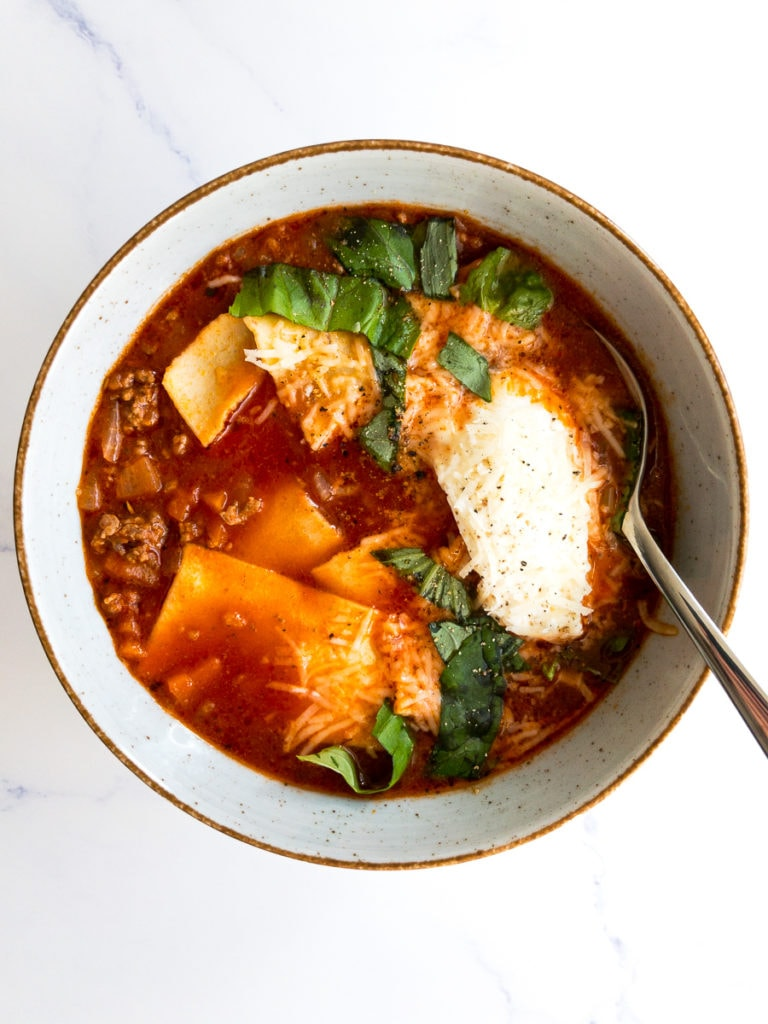 easy lasagna soup topped with fresh basil in a bowl with a spoon