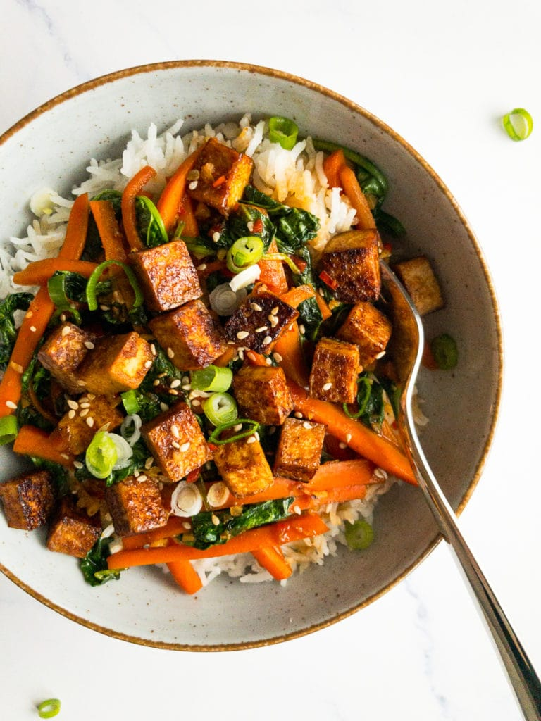 veggie tofu stir fry in a bowl with a fork