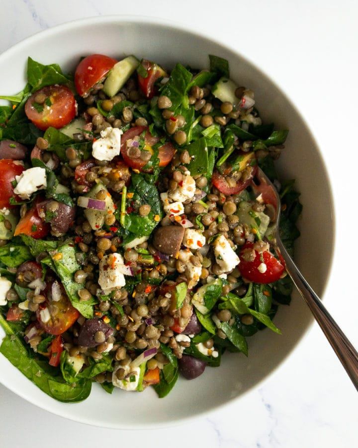 Mediterranean lentil salad in a white bowl with a fork