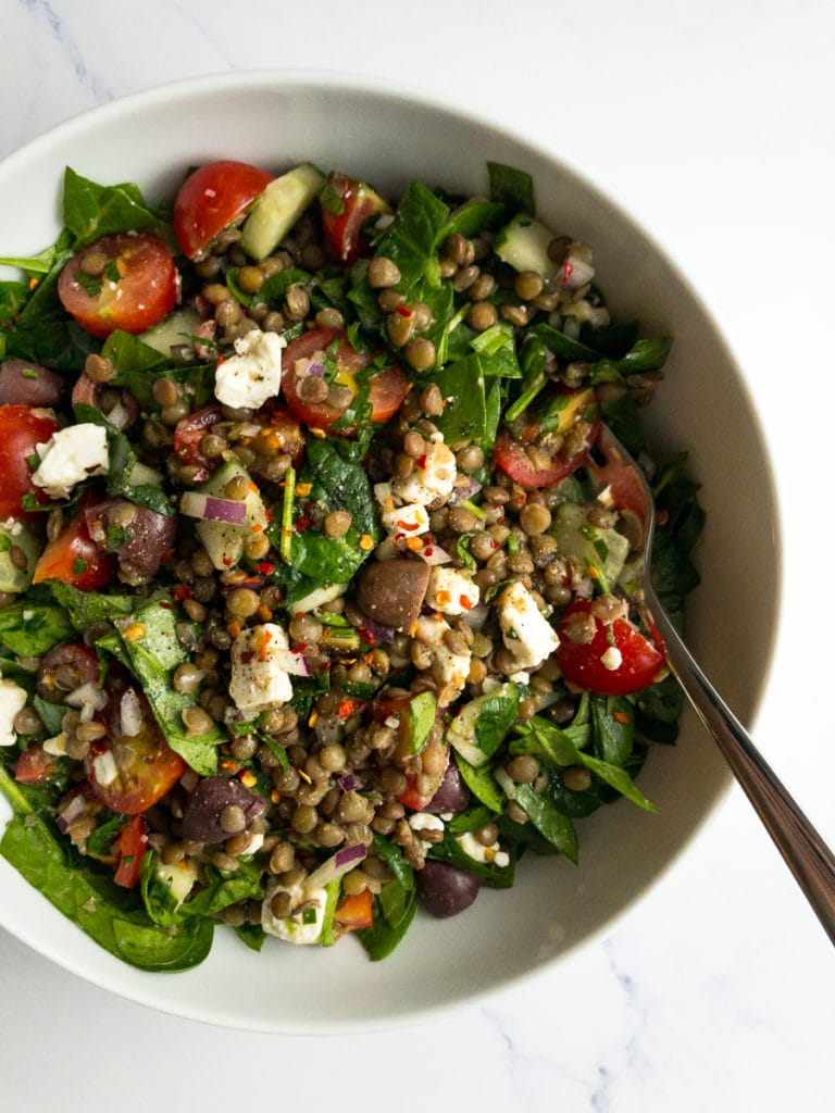 Mediterranean lentil salad in a white bowl with a fork
