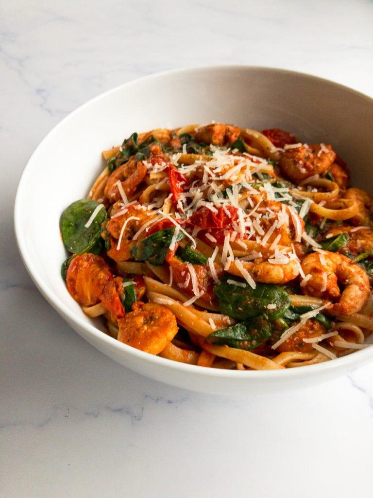spicy cajun shrimp pasta in a white bowl