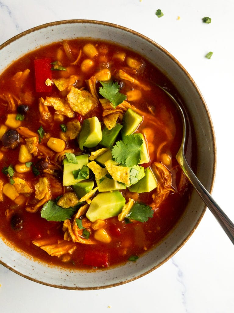 spicy Mexican chicken soup in a bowl with a spoon, topped with avocado and cilantro