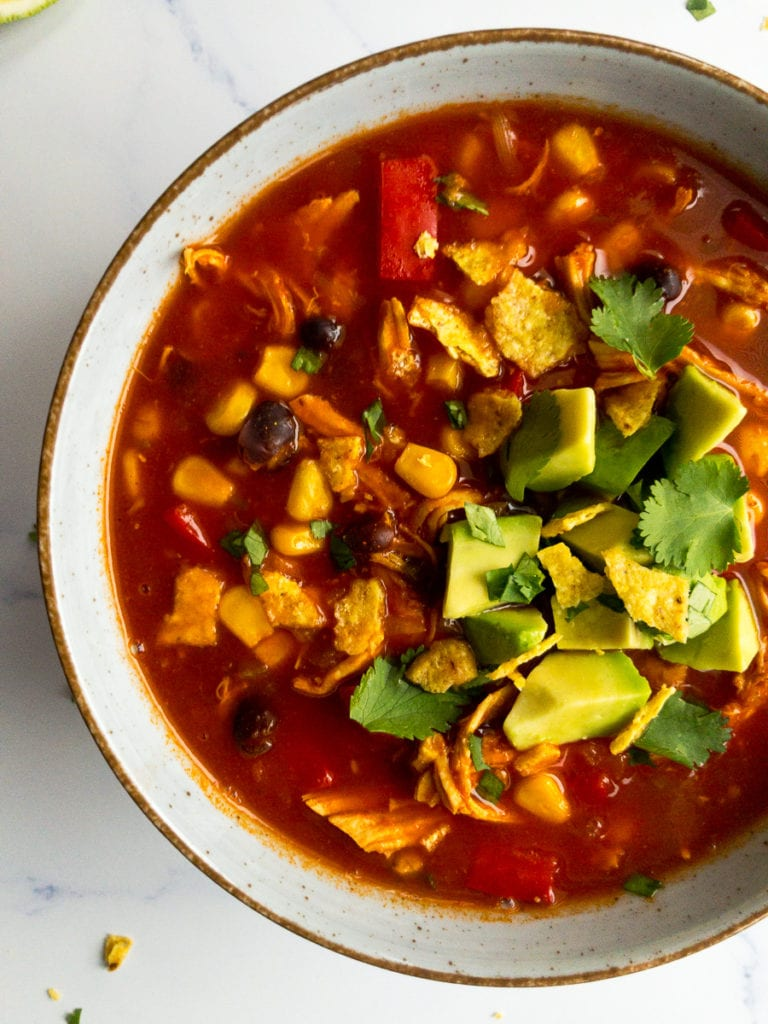 spicy Mexican chicken soup in a bowl, topped with avocado and cilantro