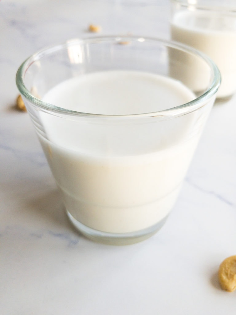 one glass of cashew milk in the front and one glass of cashew milk in the back