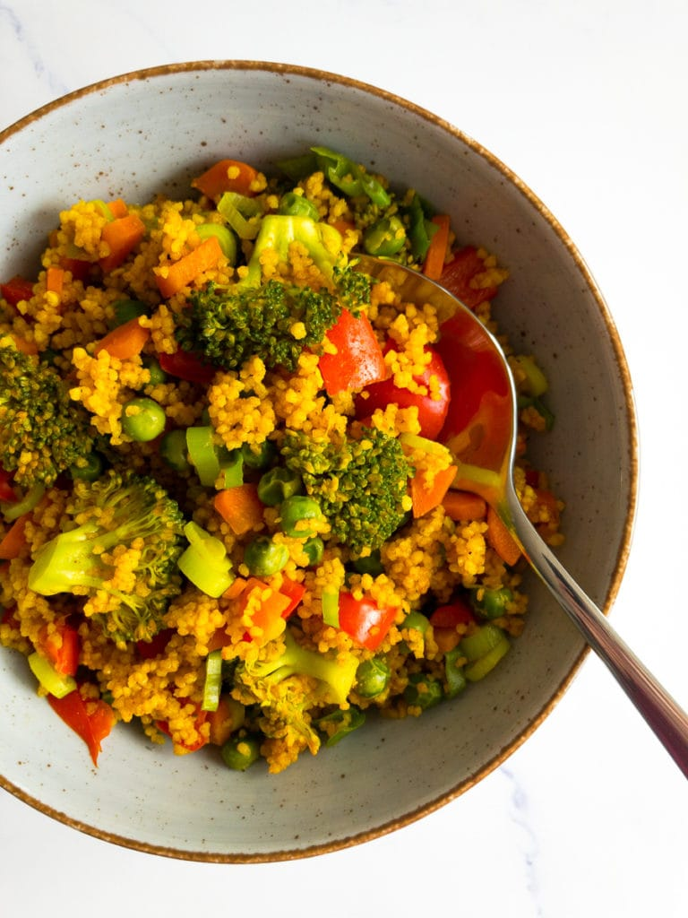 curried couscous with vegetables in a bowl with a spoon