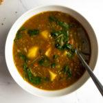 lentil potato soup in a white bowl with a spoon