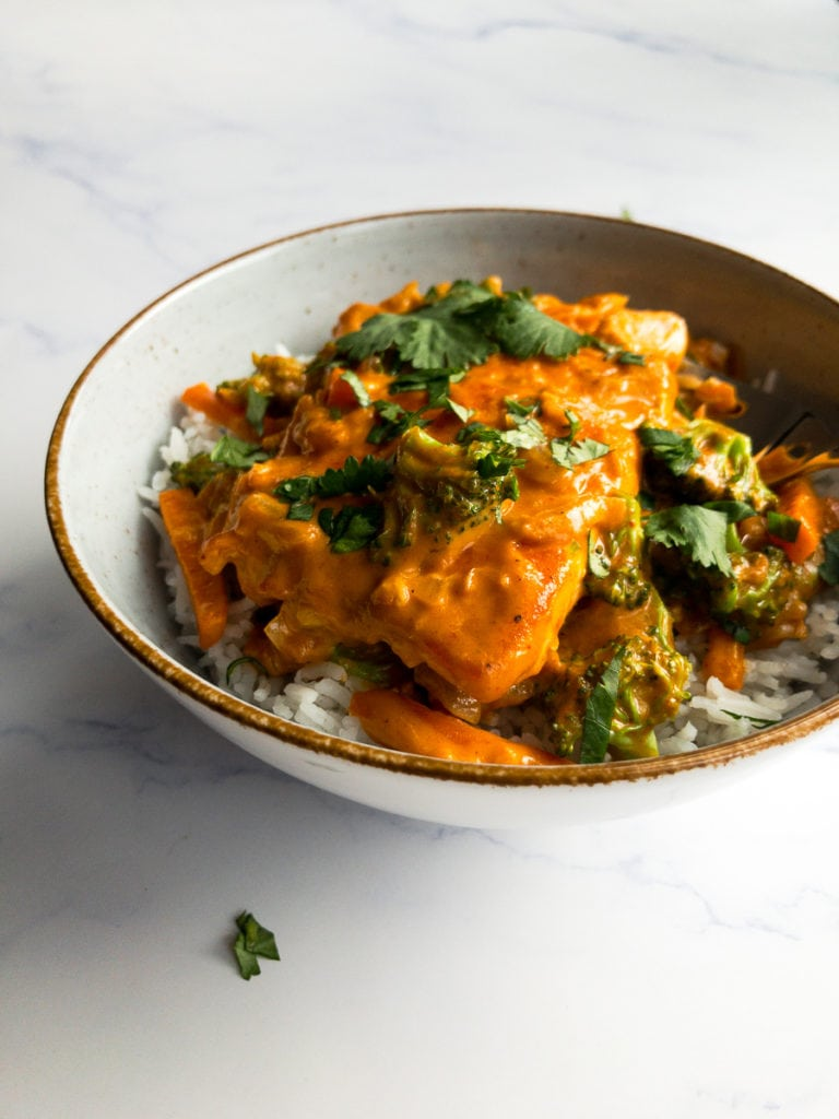 salmon coconut curry on rice in a bowl topped with cilantro