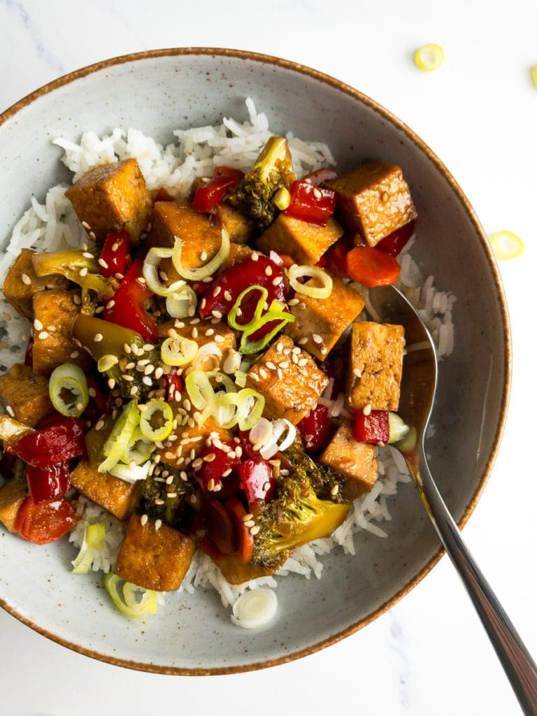 teriyaki tofu vegetable stir fry in a bowl over rice with a spoon