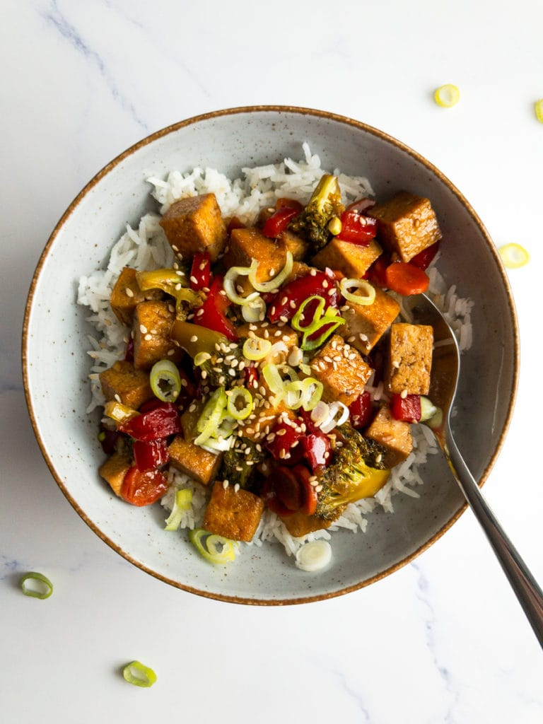 teriyaki tofu stir fry over rice in a bowl with a spoon