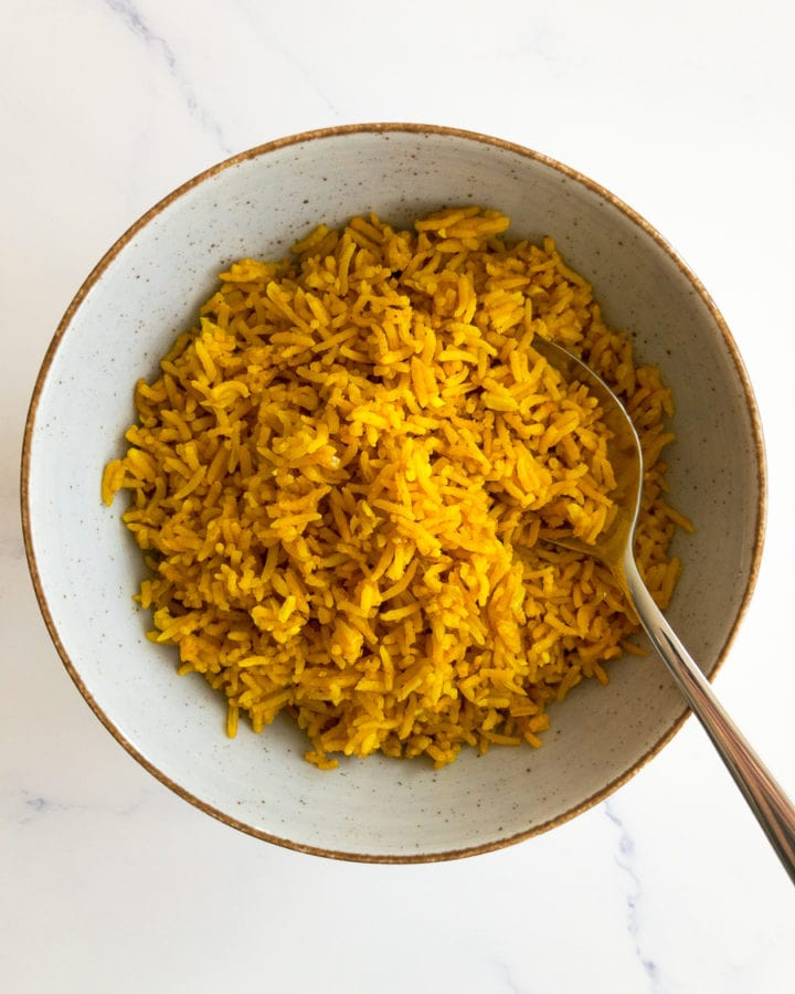 turmeric rice in a bowl with a spoon