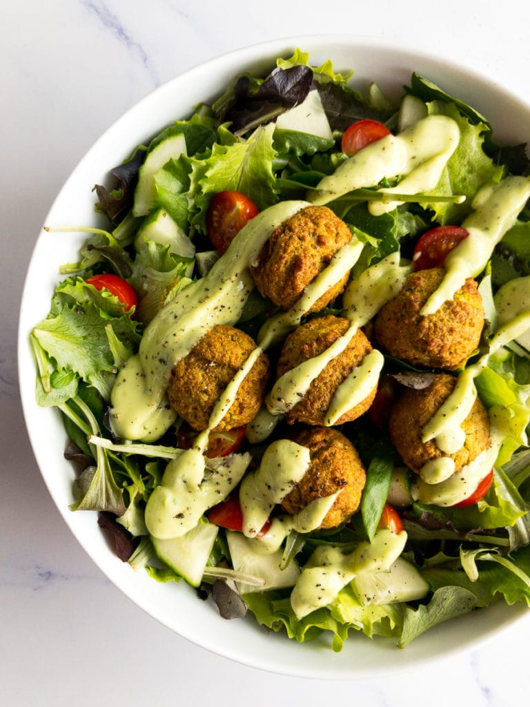 falafel over a bed of greens and avocado lime dressing drizzled on top