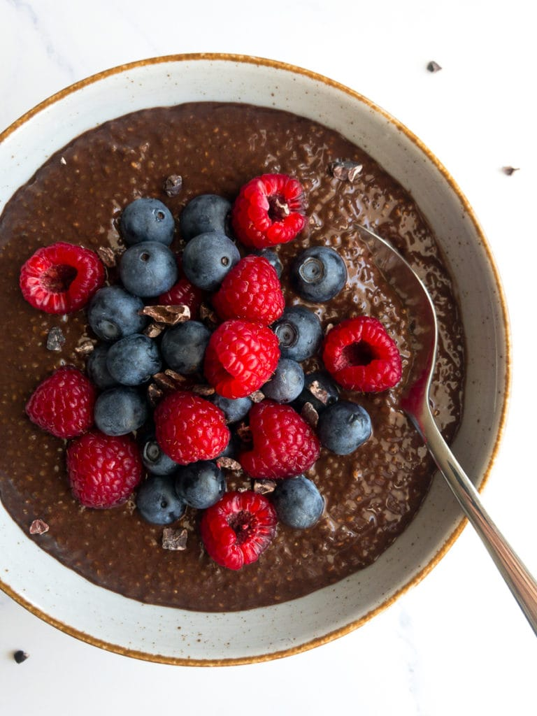 chocolate chia seed pudding topped with blueberries and raspberries in a bowl with a spoon