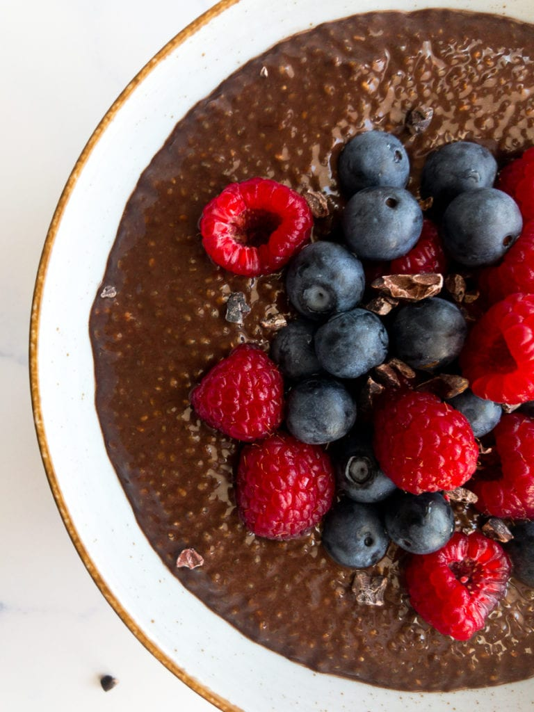 chocolate chia seed pudding topped with blueberries and raspberries in a bowl
