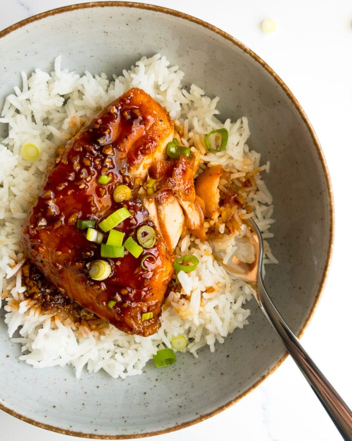 honey sriracha salmon over rice in a bowl with a fork