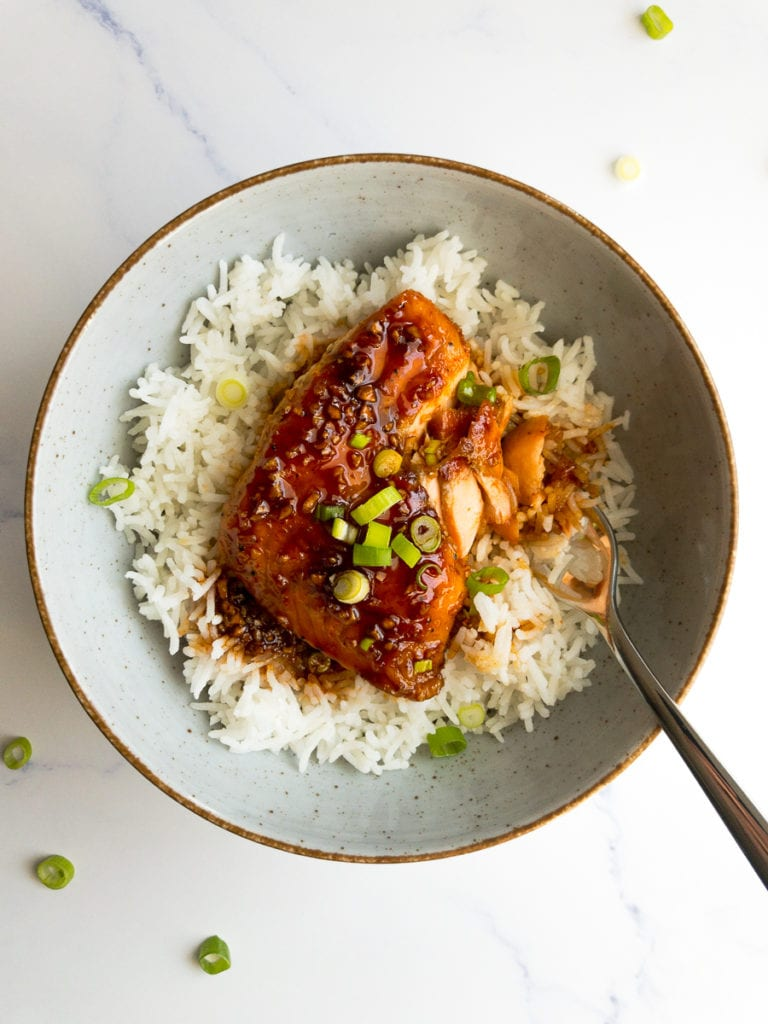 honey sriracha glazed salmon over rice in a bowl with a fork