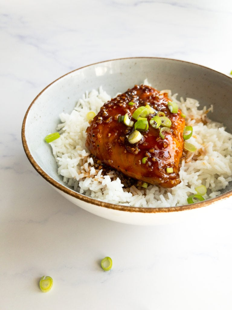 honey sriracha salmon over rice in a bowl