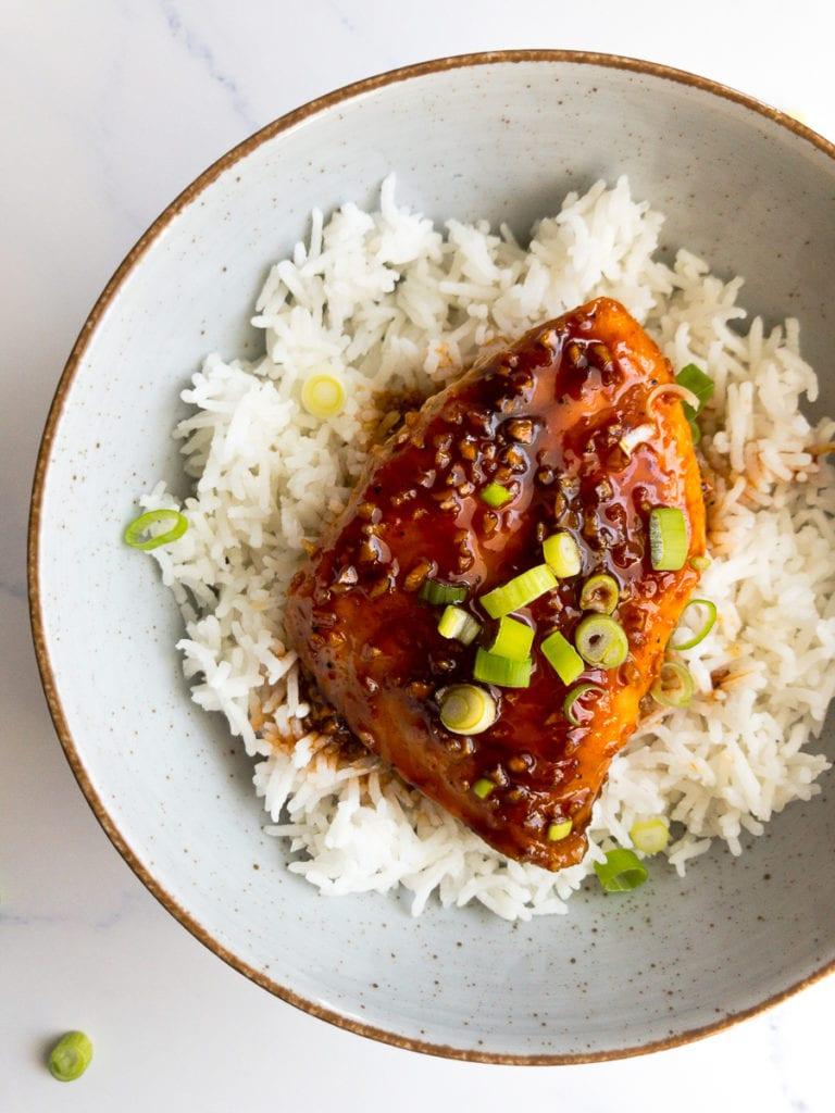 honey sriracha glazed salmon over rice in a bowl