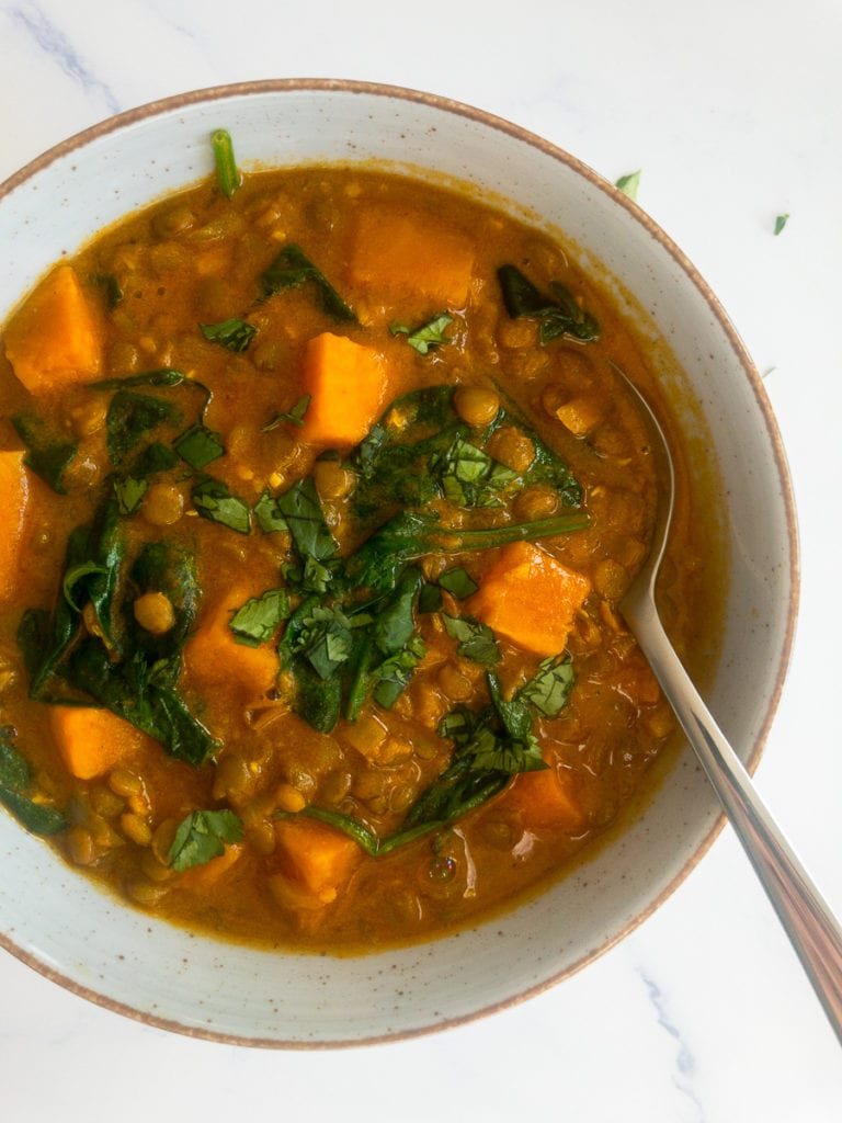 sweet potato lentil curry in a bowl with a spoon