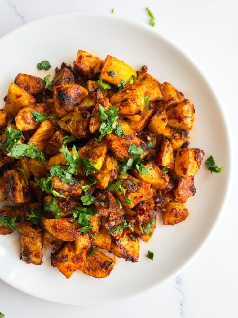 batata harra on a white plate garnished with parsley